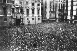 """Plaça Sant Jaume, 14 d'abril de 1931. Francesc  Macià, poques hores abans que a Madrid es proclamés la Segona República, proclama la """"República Catalana a l'espera que els altres pobles d'Espanya es constitueixin com a  repúbliques per formar la Confederació Ibèrica"""""""